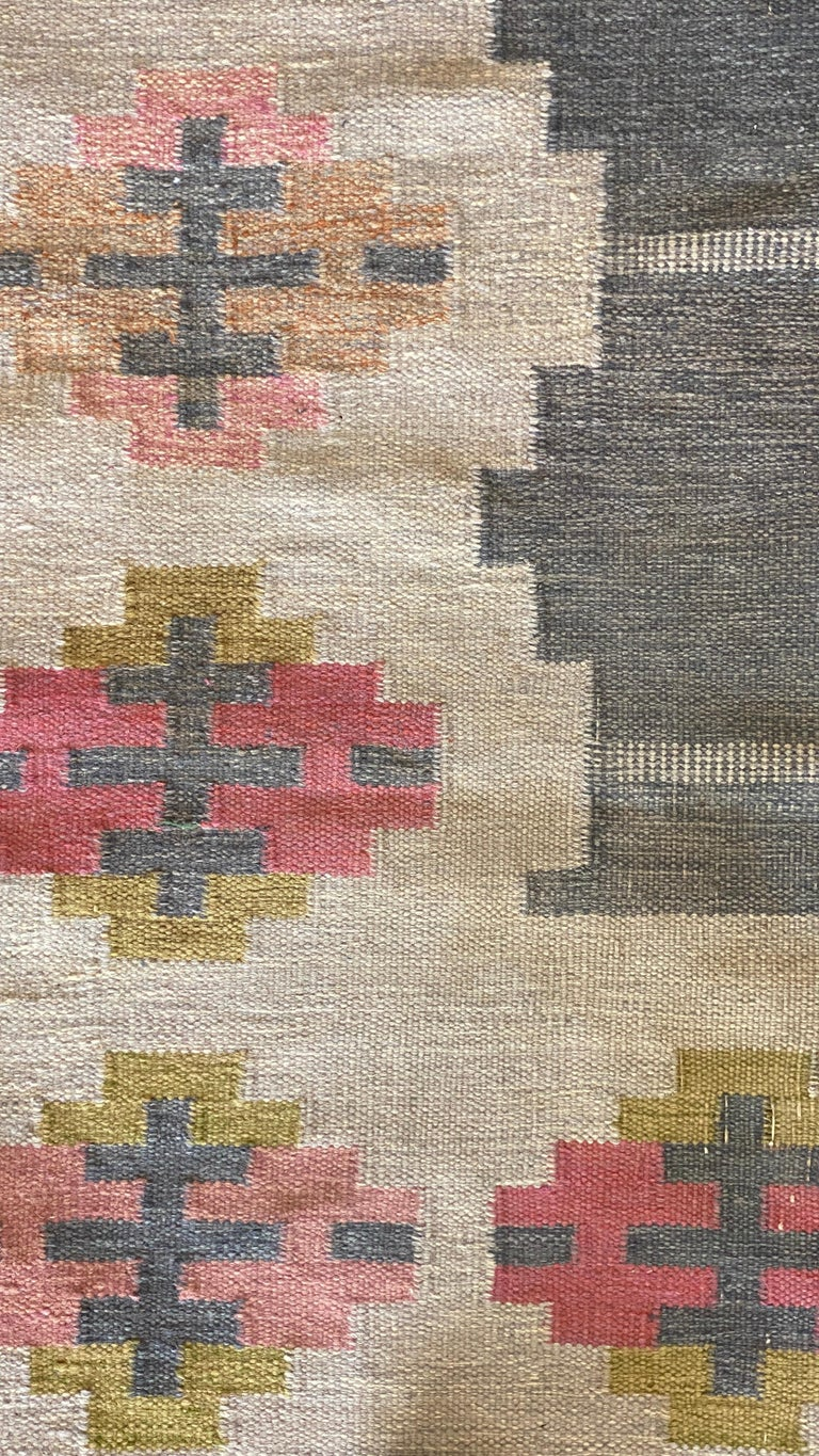 A handwoven modernist flat-weave carpet / rug by Karin Jönsson. Most likely woven in the 1950s. Handwoven in wool, using a Kilim technique. Signed.   Follows a lineage of Modernist rugs produced in Sweden throughout the 20th century. Other artists