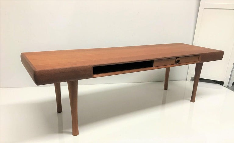 Karl Edvard Korseth teak coffee table manufactured by Ganddal Mobelfabrikk. The table has two drawers on each side with an open space on each side for magazines. Nice look for a Mid-Century Modern interior.