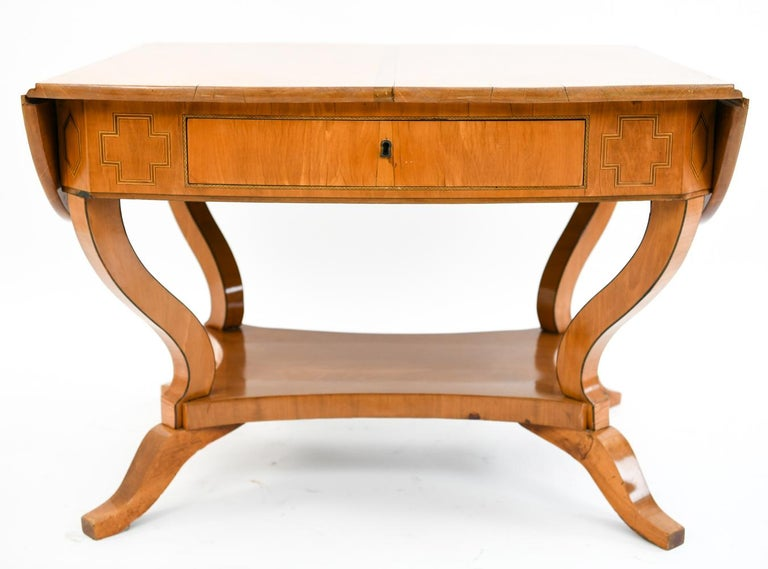 This is a handsome antique Danish Biedermeier birch desk with drop leaves. This desk features a cross motif on either side of the drawer and sits upon gracefully curved legs. This piece is in the style of Karl Johan.