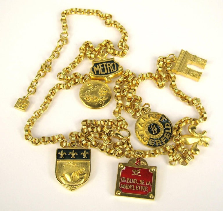 Karl Lagerfeld Gilt metal with Red Enamel with the words 14 Blvd De La Madeleine Charm Necklace or belt. Charms include 14 Blvd De La Madeleine/ 5 francs/ meme dimanchie et petes / Metro. I have more of this set listed on my storefront. It  measures