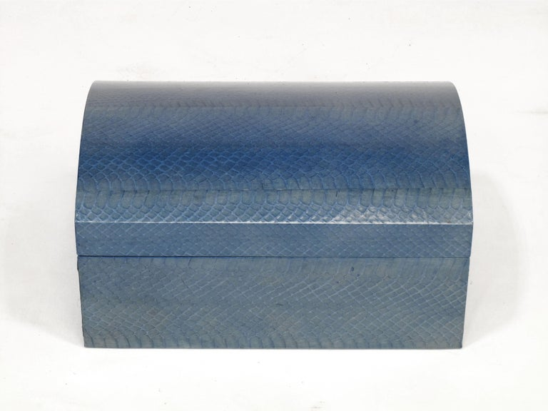 Elegant and edgy python snake skin covered box by Karl Springer. The top is arched and the interior is blue suede. Chrome piano hinge allows the box to open fully. The azure blue python hide has color variation as you would expect from a dyed,