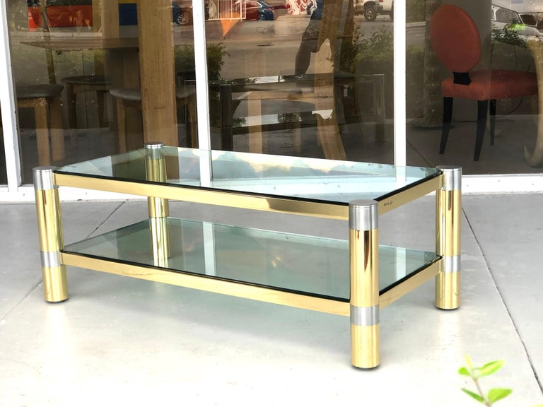 A polished brass and brushed steel coffee table by Karl Springer. The table is a double decker, with 2 thick glass tops.