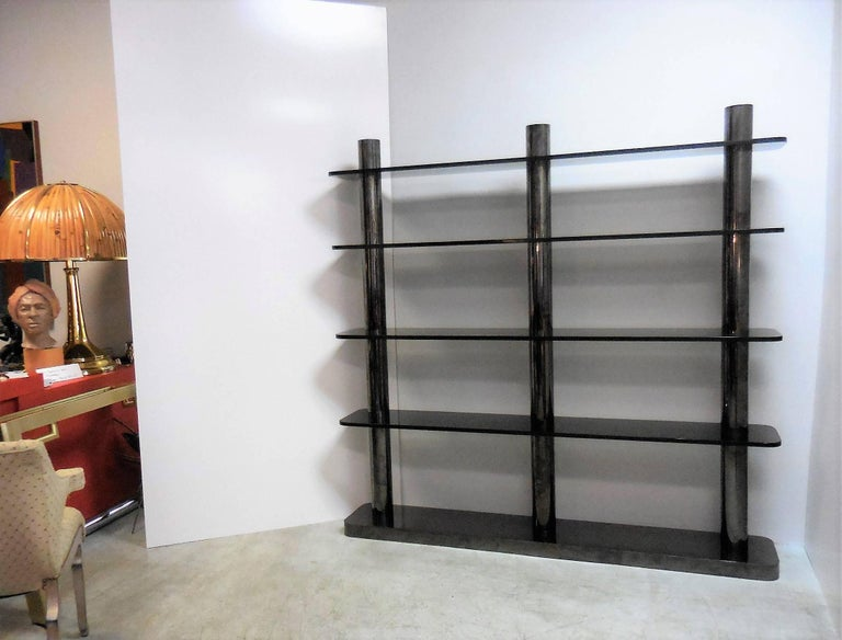 A rare Karl Springer freestanding bookcase or etagere. Bronze columns with gun metal finish and smoked glass shelves. The design is miraculously simple and yet sexy, bold and functional. Certificate of authenticity included.
