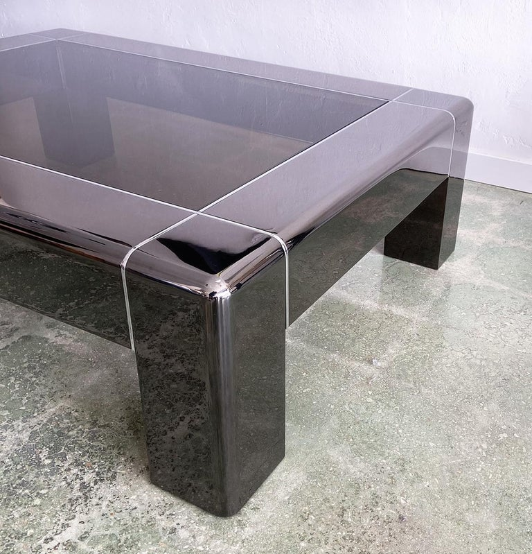 Karl Springer cocktail or coffee table in gunmetal and polished steel 1980s In excellent, like-new condition, parsons style with smoked glass. Black oxide reflective finish with rare polished stainless steel banding accents. One of the finest we've