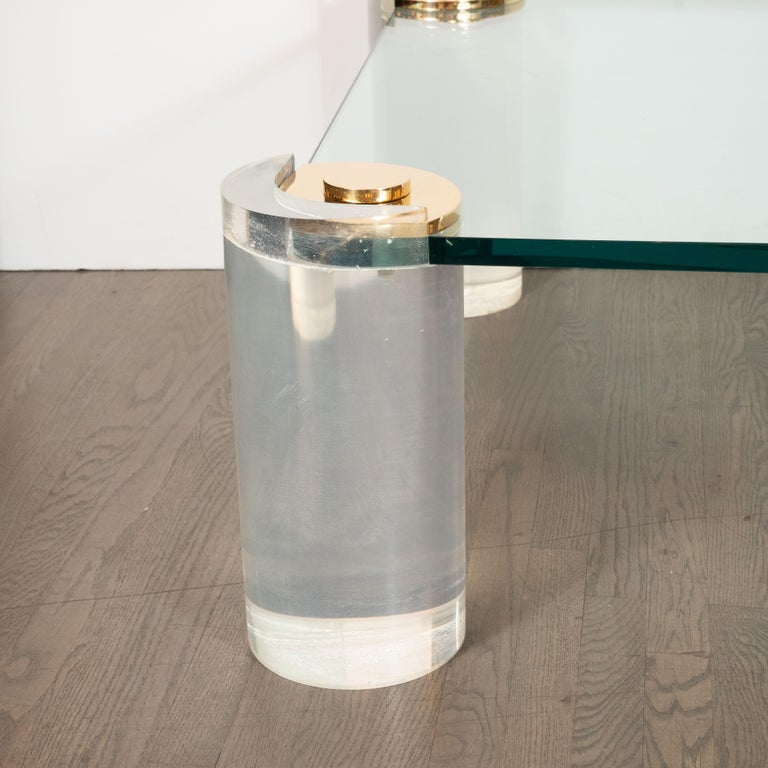 This sophisticated cocktail table was realized by Karl Springer- one of the most important and influential designers of the 20th century, circa 1985. It features cylindrical Lucite legs that attach to a rectangular glass top with rounded corners via