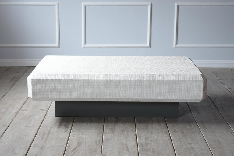 This Karl Springer Floating grass cloth coffee table is in great condition and has a large rectangular top covered in grasscloth fabric that has been newly painted in an off-white color finish. The top rest on a sturdy floating base made from wood