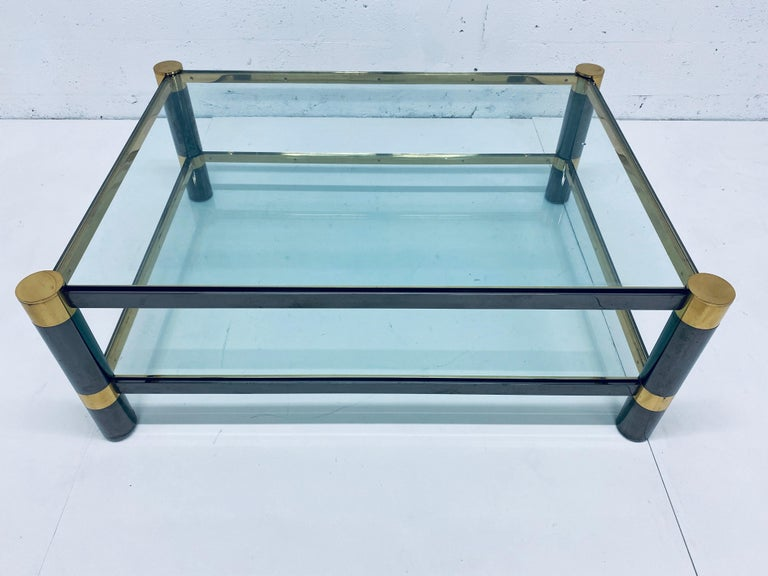 """Two-tier coffee or cocktail table rendered in gunmetal, brass and glass by Karl Springer, signed.  Glass shelf height Upper - 17-3/8"""" Lower - 7-1/2."""