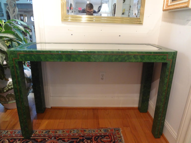 Stunning Karl Springer inspired green marbleized lacquer and brass console table with mirrored top. This versatile and unique free standing Parsons style console is decorated on all sides accented with brass strip and can be used floating in a room.