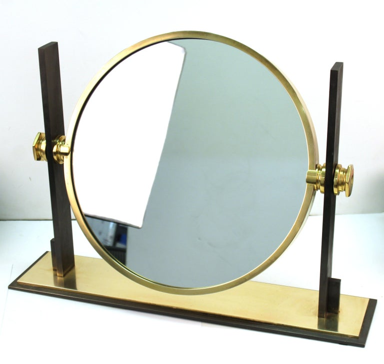 Modern round vanity or table mirror designed by Karl Springer. The piece is made with a brass and heavy steel structure. Mirror revolves and can flip from the convex side to a flat regular side. In great vintage condition with age-appropriate wear.