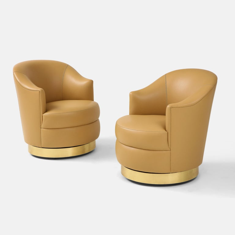 Karl Springer documented rare pair of swivel chairs in camel leather with brass bases, USA, 1980s. This incredibly chic pair of swivel chairs has been fully restored and newly reupholstered in Edelman camel leather. Original label on the bottom of