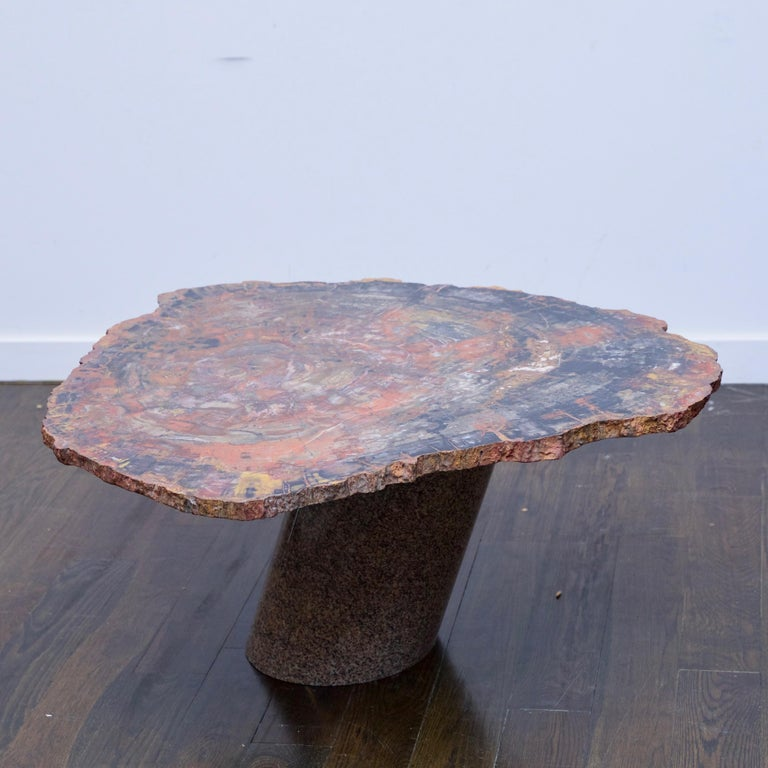 A petrified wood table top was purchased from Karl Springer for this custom piece by an unknown firm. Table is made from a cross section of petrified wood resting on a granite base.