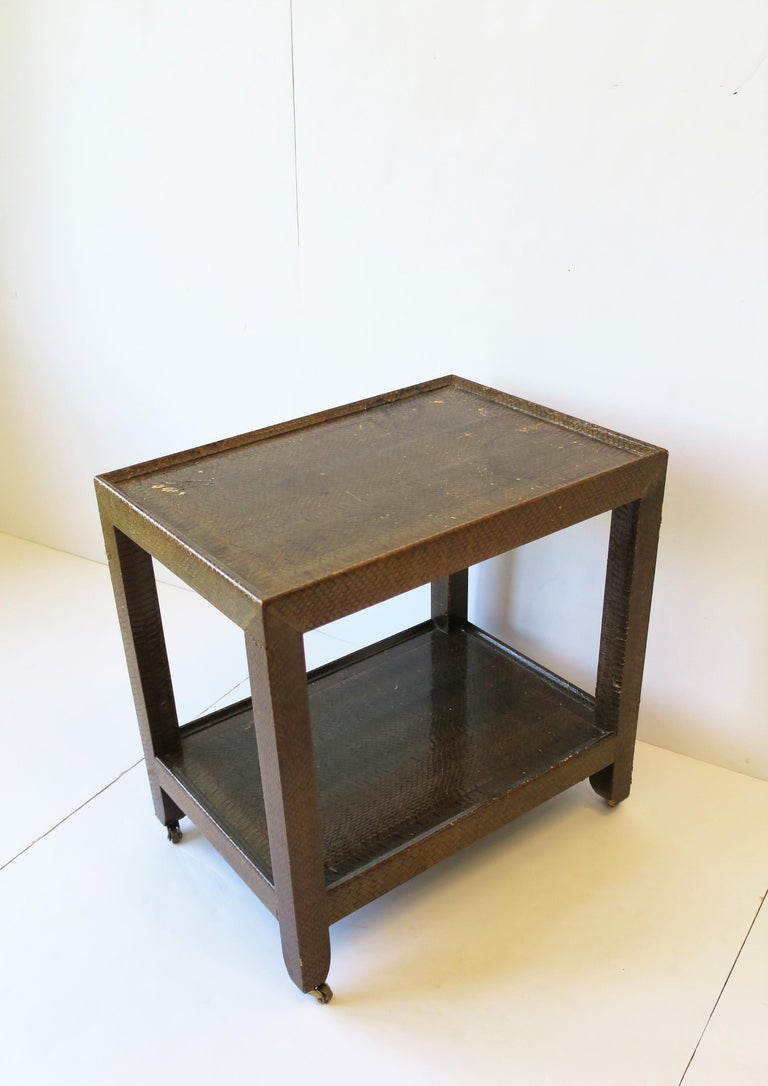 A beautiful Postmodern 'telephone' side or end table by designer Karl Springer, 1990. Table is covered in a beautiful authentic snakeskin in a medium brown and supported by small brass caster wheels. There's a lower shelf area for books, etc. Table
