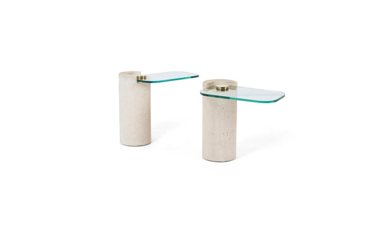 Pair of sandstone drink tables with polished brass hardware and cantilevered glass. Karl Springer, 1980's. New glass
