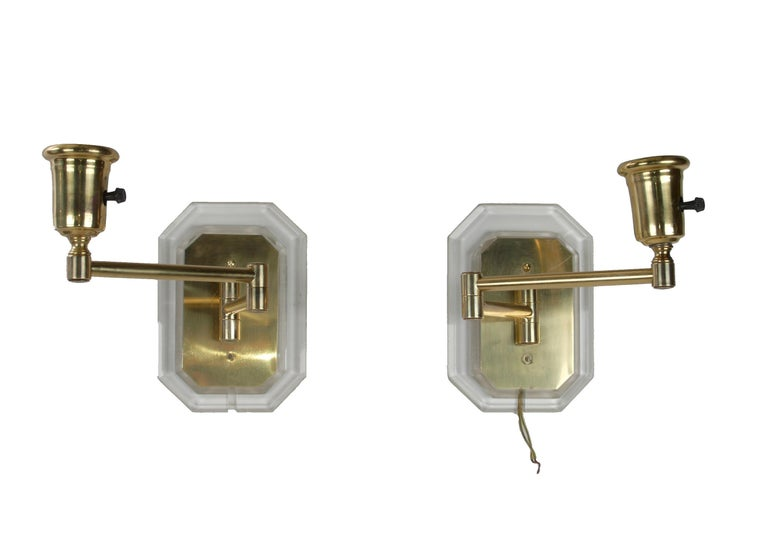A pair of Mid-Century Modern Lucite and brass swing wall sconces in the style of Karl Springer. Wired for the U.S. and each uses a max. 60 wattage light bulb.