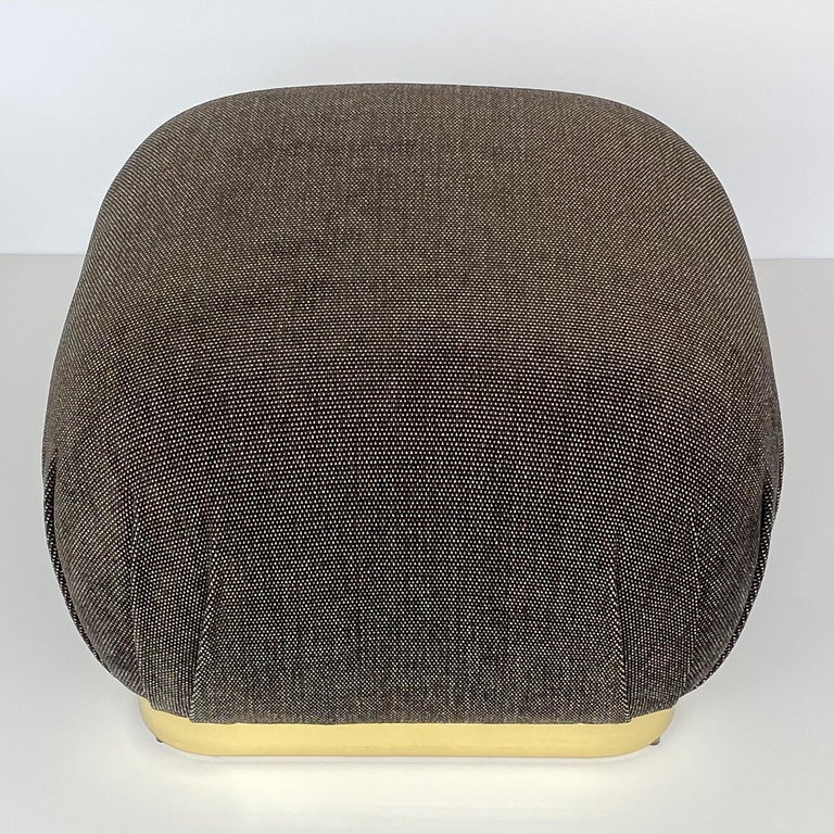 A Karl Springer style brass soufflé pouf ottoman, circa 1970s. This ottoman has been newly upholstered in a viscose blend chenille fabric in a warm gunmetal gray and white dot. New foam throughout. 2