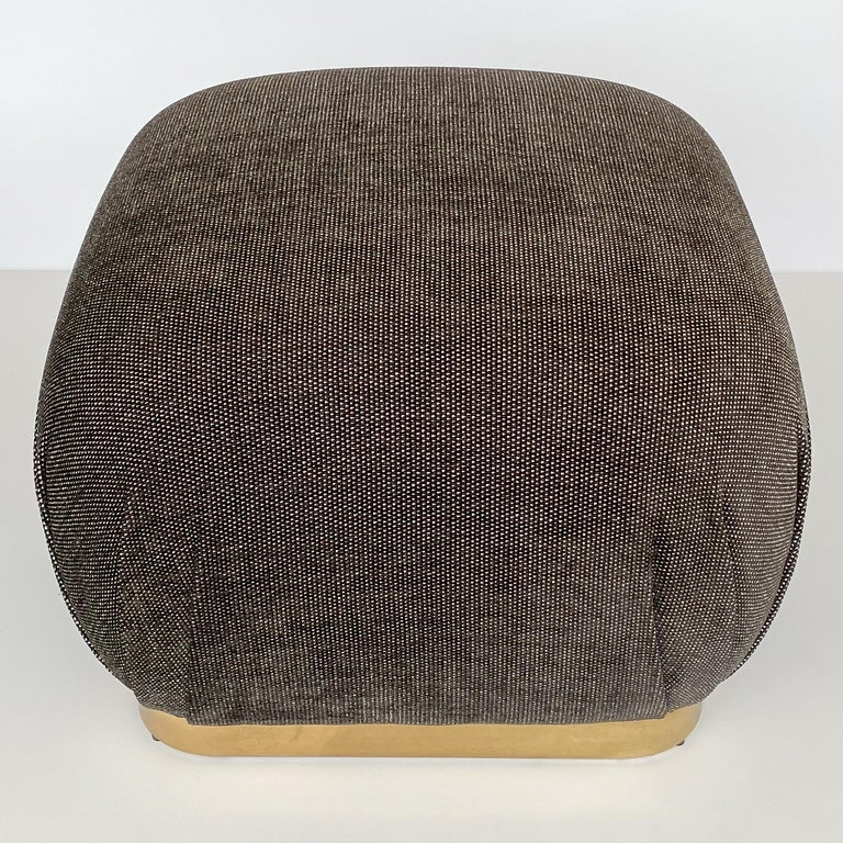 A Karl Springer style bronze tone soufflé pouf ottoman, circa 1970s. This ottoman has been newly upholstered in a viscose blend chenille fabric in a warm gunmetal gray and white dot. New foam throughout. 2