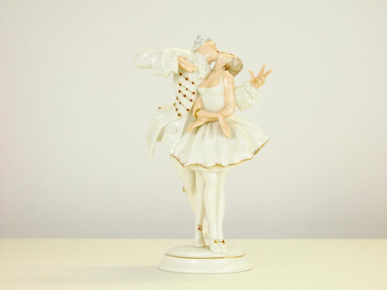 Vintage midcentury fine porcelain figurine depicting a romantic dancing couple in romantic dressing just starting to kiss.  The figurine is mostly white glazed with golden accents and has hand painted body parts. It dates from the period 1955-1969