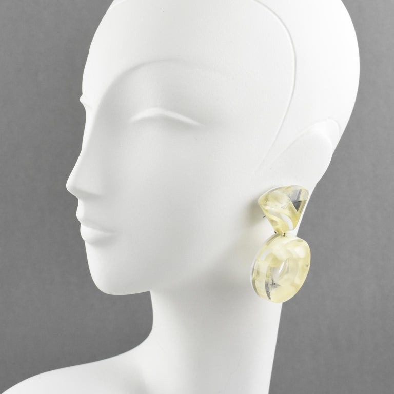 Oversized lucite clip-on earrings designed by Harriet Bauknight for Kaso. Large donut dangling shape with a geometric design featuring dimensional multilayer Lucite with inclusions. Contrasted pattern in mirror, frosted and clear texture. Winter