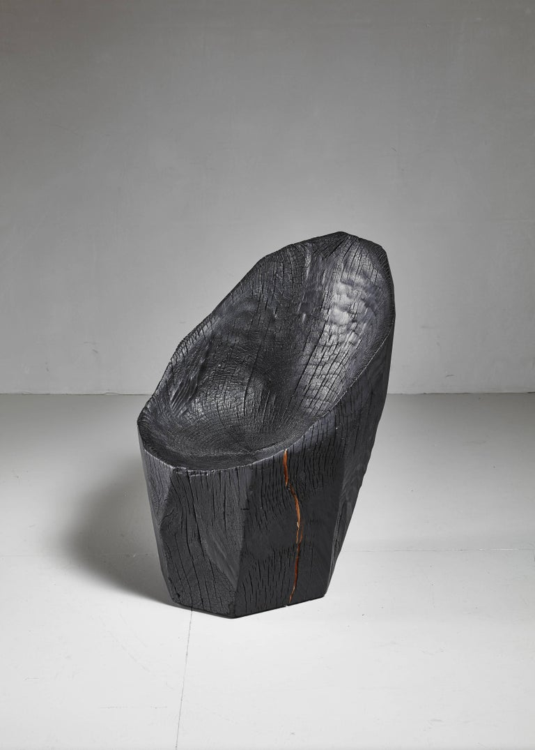 An 'Ausgebrannt' chair made from a solid piece of oak from a naturally fallen tree by Belgian artist Kaspar Hamacher.