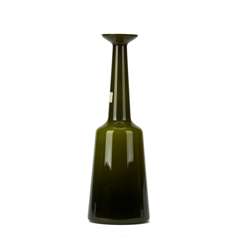 A very rare Danish Kastrup Holmegaard cased glass lamp base cased in green glass with a slightly tapered base leading up to a chimney neck with flared top. The lamp base has an original drilled hole to the lower edge and retains paper labels to the