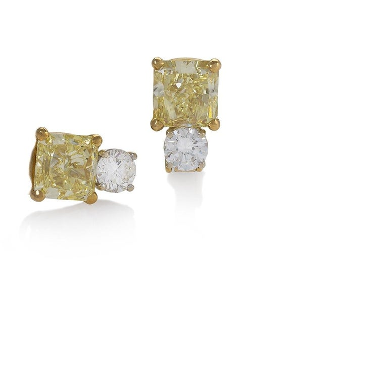 A pair of platinum earrings by Kauffman de Suisse featuring two cut-corner square cut fancy yellow internally flawless diamonds that weigh 3.24 carats and 3.04 carats respectively, and accented by two round brilliant diamonds, each weigh