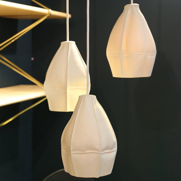 To create the Kawa pendant for Souda, Luft Tanaka slip cast porcelain directly into dozens of leather molds resulting in highly-unique ceramic shades. Once Luft arrived at the perfect shape, Souda worked with an industrial production partner where