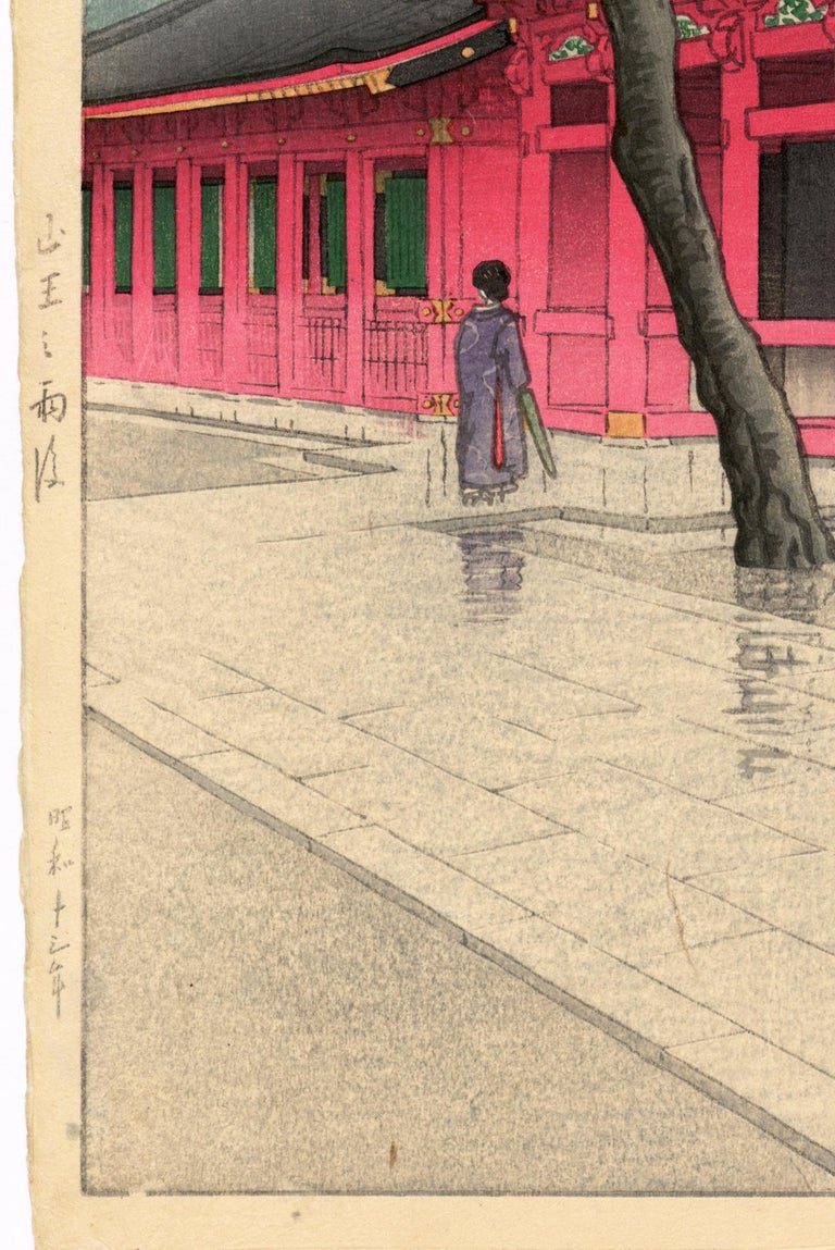 The rain has just stopped, leading the single visitor this Tokyo shrine to fold her umbrella. The paving stones are slick with rain, and the shrine colors are softly muted to match the tones of an overcast day. Works by this artist are often faded