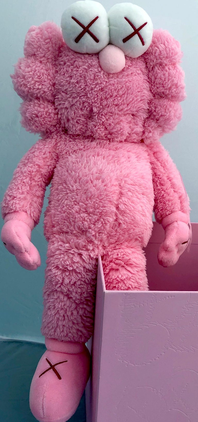 KAWS BFF Plush Companion (KAWS Pink BFF Plush)  New in its original packaging. As only 3,000 pieces were produced, the pink plush was sought-after and coveted by fans and collectors alike, and while most were unable to get their hands on the piece.