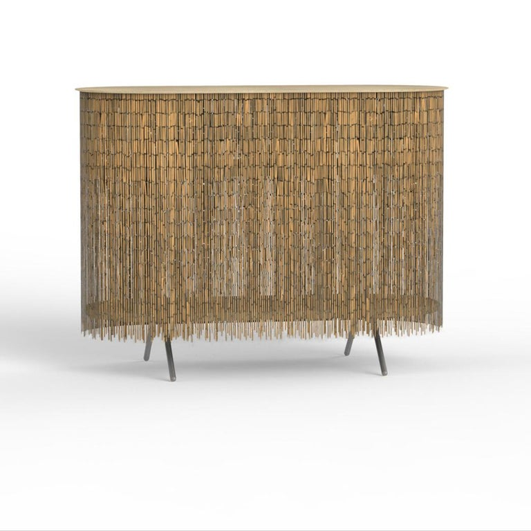 Keefer is a credenza that alludes to the objects stored within its shelves, yet obscures their identity through its bamboo-beaded skirt. The skirt masks the vertical supports, creating the allusion of floating shelves. The interior can be accessed