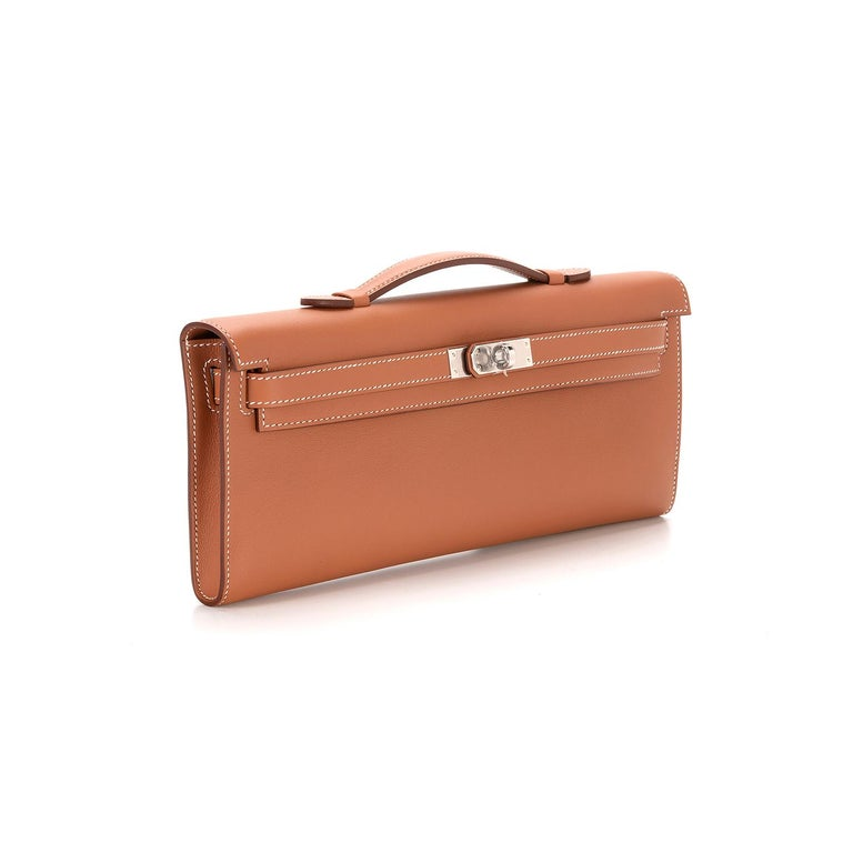 Crafted in France from supple swift leather, this Gold Kelly Cut Clutch Bag by Hermès features contrasting stitching, front straps and a top flat handle. The toggle closure is accented by silver-tone palladium hardware and opens to reveal an