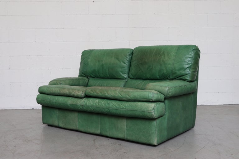 Kelly green leather love seat sofa. Well worn with visible wear and patina. In original condition with wear consistent with age and use.