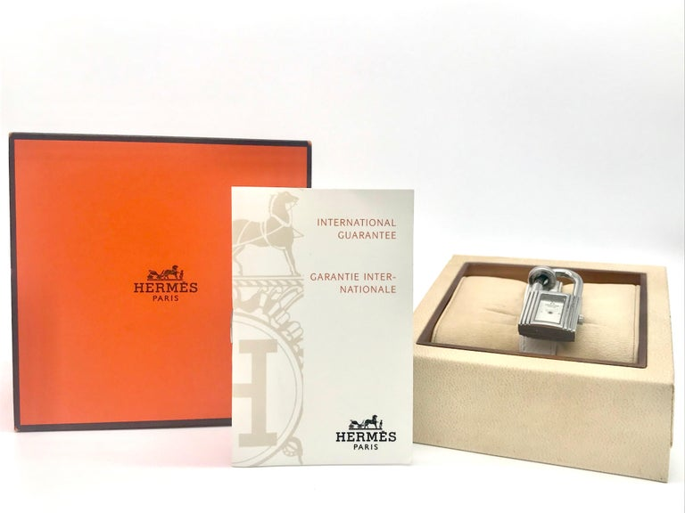 Kelly Hermes Watches White calfskin Bracelet  stainless steel Dimensions of the housing 20 x20 cm  With certificat and Original Box  Kelly watch with padlock shape on a moblile brass ring, index 4, quartz movement, on buckle adjustable buckle