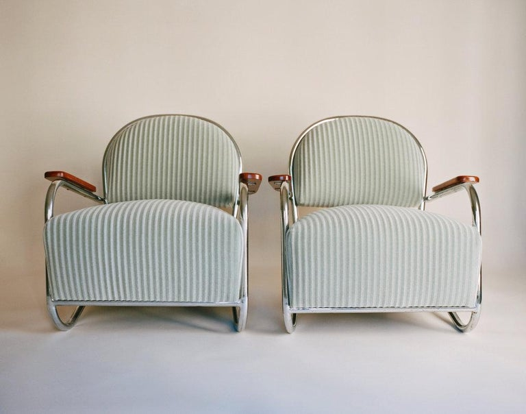 A pair of chromium-plated tubular steel lounge chairs upholstered in thick, sage green corduroy with lacquered walnut armrests. Weber designed these chairs in 1934 for the Lloyd Manufacturing Company in Menominee, Michigan. These chairs debuted at