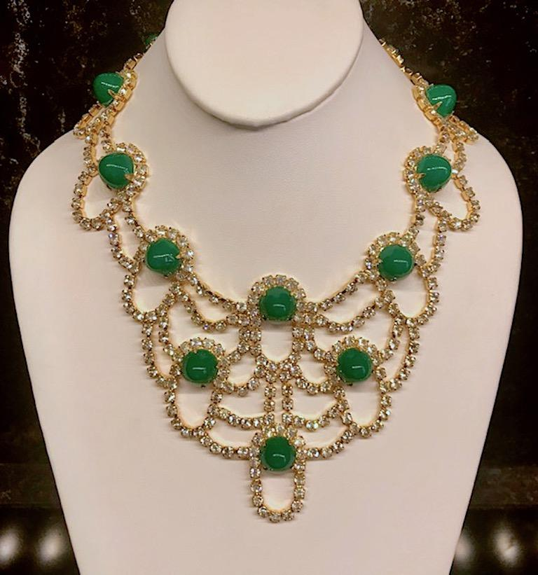 A fabulous Kenneth Jay Lane rhinestone and green cabochon bib necklace from the 1980s. Bright shiny gold plate setting with crystal rhinestones and lucite green gumdrop cabochons. Wearable length of 16 inches. Front drop of 3.75 inches. Back