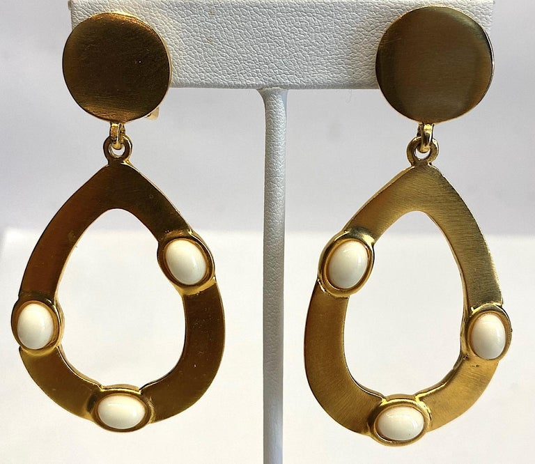Kenneth Lane 1980s satin gold tone pear shape pendant hoop earrings with oval white cabochons. Each earring is 1.38 inches wide and 2.75 inches long. The top round button has a clip back and measures .63 of an inch in diameter. The pear shape