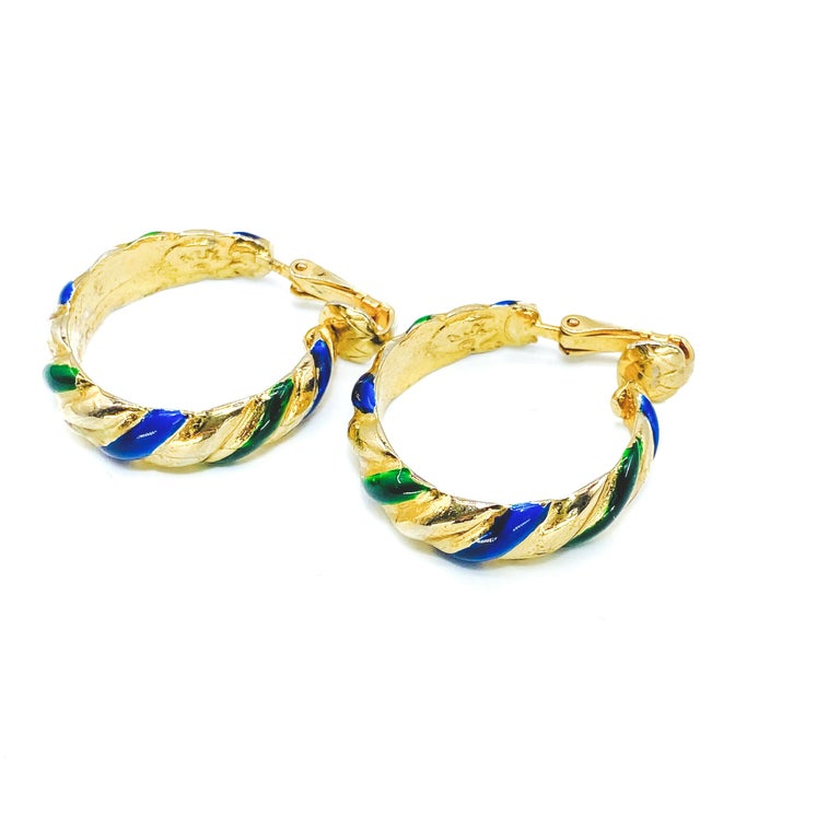 Kenneth Jay Lane 1980s Clip on Hoop Earrings  Detail -Made in the USA in the 1980s -Crafted from 1980s -Inlaid with blue and green enamel  Size & Fit -Approx 1 inch across  -Strong clips  Authenticity & Condition -Fully examined and authenticated by