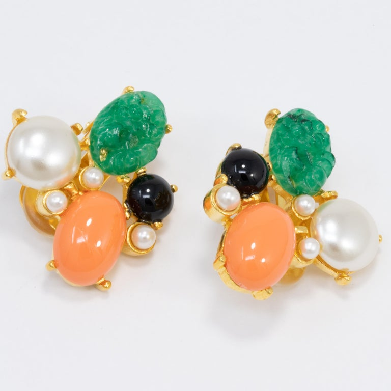 A pair of golden earrings by Kenneth Jay Lane, featuring prong-set faux pearls, carved jade, and cabochons.  Hallmarks: KJL, Made in USA  Gold plated.