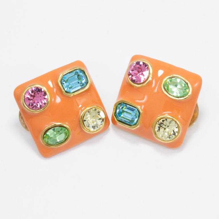 A pair of clip on earrings by Kenneth Jay Lane. Each gold-plated earring is painted in coral orange enamel, and decorated with colorful crystals.  Crystals: Aquamarine, peridot, rose, topaz  Tags, Marks, Hallmarks: KJL, Made in USA