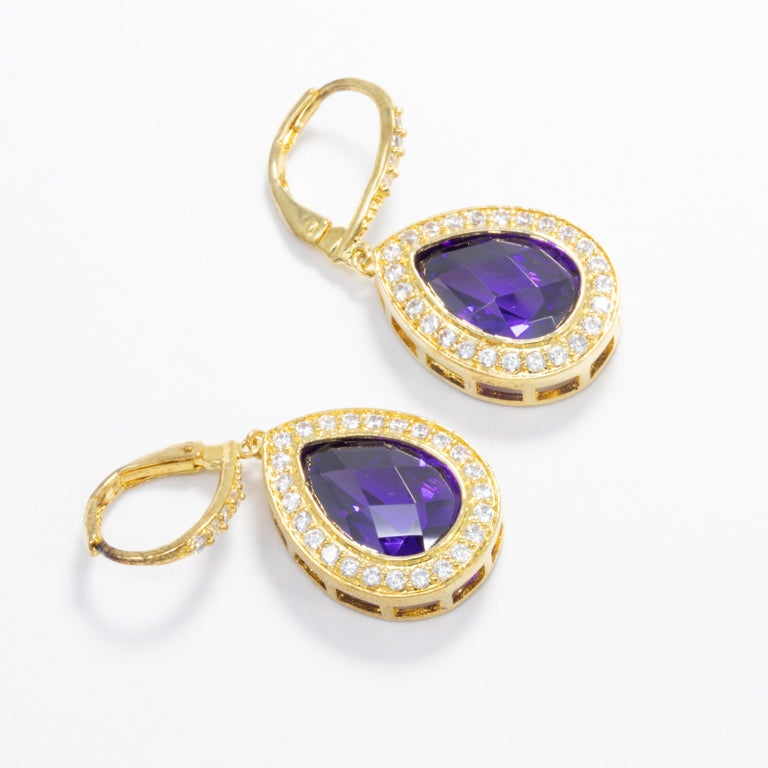 Add some sparkle to your outfit with these gold plated pear dangle earrings by Kenneth Jay Lane.  Clear and purple amethyst cubic zirconia crystals. Lever hook closure.  Marks/Hallmarks: KJLane  CZ by Kenneth Jay Lane line. Designed in New York.
