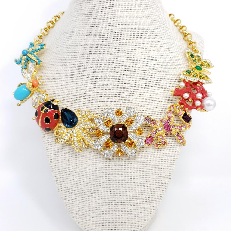 Kaleidoscope necklace by Kenneth Jay Lane. Signature KJL designs linked together to form a dazzling statement necklace! Colorful starfish, fly, ladybug, butterfly, coral, flower, and leaf motifs.  Features faux pearls, painted enamel, cabochons and