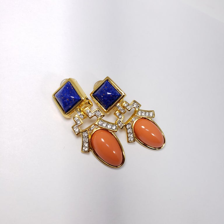 Stylish art deco-style earrings by Kenneth Jay Lane. Each earring features a faux lapis lazuli and coral cabochon, accented with crystals. All set in gold-plated metal.  Hallmarks: KJL, Made in USA