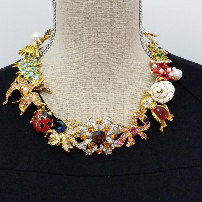 Kaleidoscope necklace by Kenneth Jay Lane. Famous whimsical KJL designs linked together to form a dazzling statement necklace! Colorful dragonfly, butterfly, coral, seashell, monkey, bow, flower, ladybug, and spider motifs. The motifs are linked