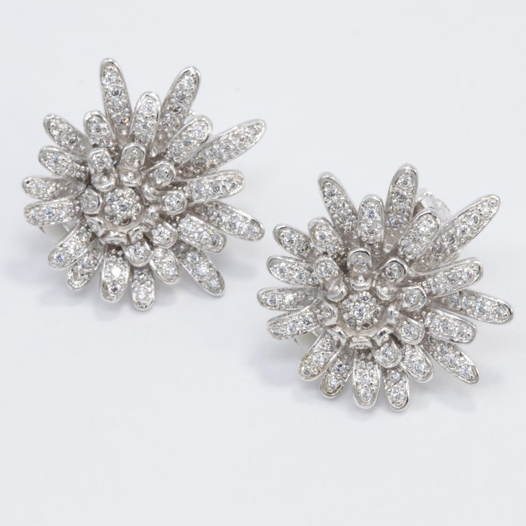 Add some sparkle to your outfit with these flower button clip on earrings by Kenneth Jay Lane!  Clear cubic zirconia crystals. Silver tone.  Marks/Hallmarks: KJLane  CZ by Kenneth Jay Lane line. Designed in New York. Made in China.