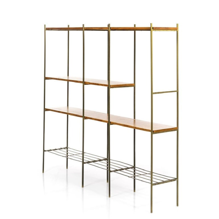Midcentury Kenneth Lind room divider made with vintage walnut and metal, circa 1950s. Fair condition, some of the bottom shelf is slightly bent as seen in the photo, and the bottom left corner must be reattached, but remains functional.