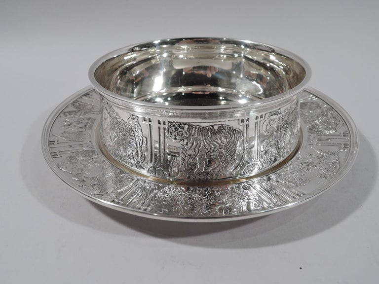 Edwardian sterling silver baby bowl on plate. Made by Kerr in Newark. Bowl has gently upward tapering sides and plain flat rim. Plate has deep plain well. Acid-etched menagerie with lions and tigers and bears as well as domestic critters like cats
