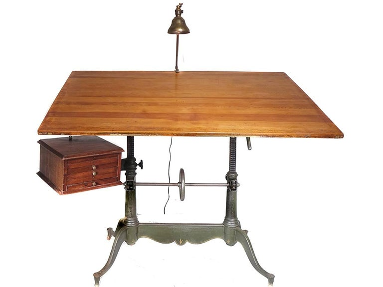 This is an exceptional antique cast iron double pedestal drafting table by Keuffel & Esser, with a beautiful detailed base having a centre wheel for height adjustment, and a locking mechanism for tilt adjustment. This handsome table also has the