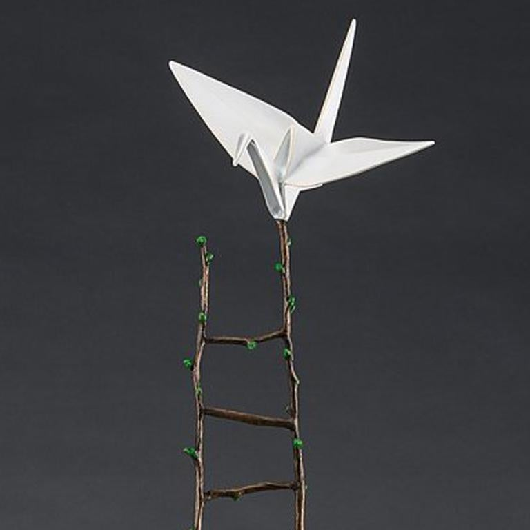 Painted stainless steel and patinated bronze  An origami crane perches at the top of a long ladder. A lasting symbol of good fortune, love, and happiness, the crane is poised for flight.   Kevin Box is an internationally-renowned sculptor working in