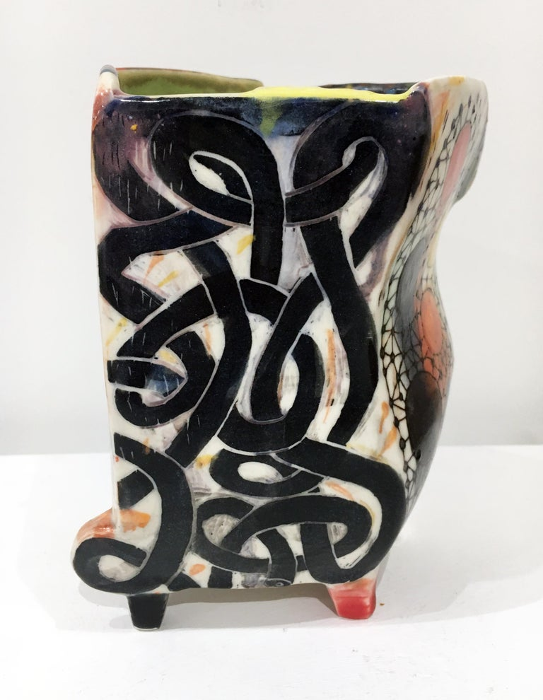 Kevin Snipes creates ceramic vessel forms that act as canvases for self referential narratives that are brought to the viewer through a combination of illustration and symbolism, obscure glyphs, and comical/whimsical motifs. Within the discipline of
