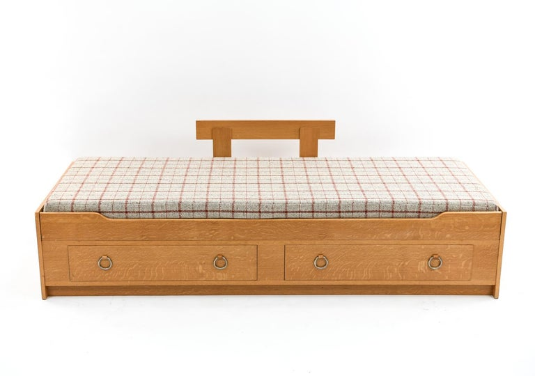 Cozy up on this Danish midcentury oak daybed manufactured by Køge Maskinsnedkeri. Featuring a set of double drawers with round metal and leather pulls perfect for storing books, clothing, linens or any items of your choice.