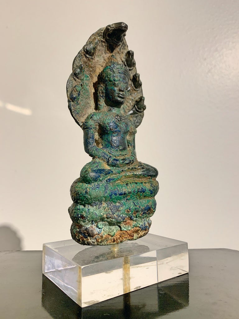 A wonderful small Khmer cast bronze figure of the Buddha sheltered by a Naga (Buddha Muchalinda), Angkor Period, style of the Bayon, late in the period, 14th century, Cambodia.  This small Khmer cast bronze sculpture is known as Buddha Muchalinda,